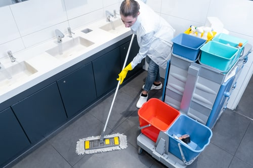 Cleaning lady mopping the floor in restroom